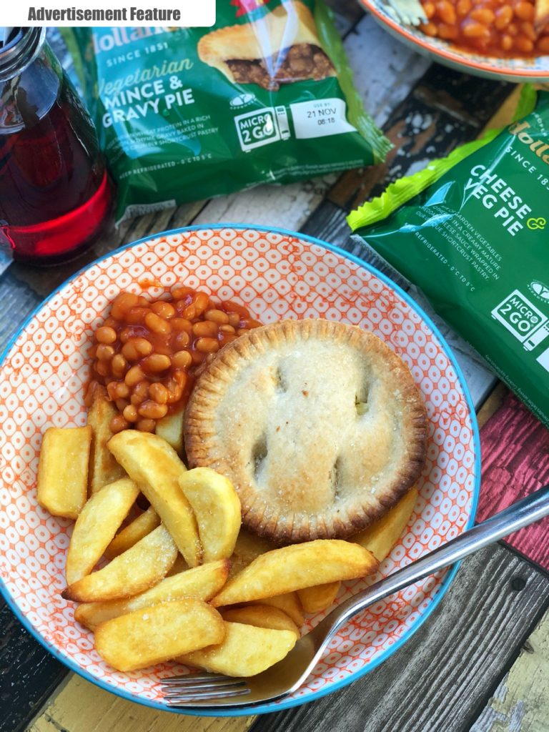 vegetarian Holland's pie with chunky chips and baked beans on a colourful table with two vegetarian holland's pies still in the packets and bottles of vimto with straws