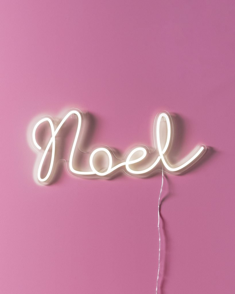 noel neon wall light against a pink wall