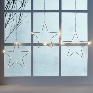 white lit up wire stars hanging from misty window and bare twigs by the window pane