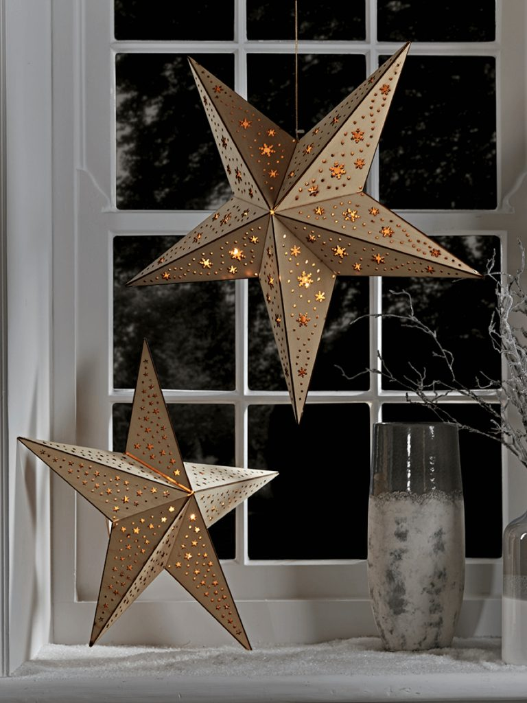 plywood wooden stars with glowing white light shining through cut out holes - hung in a wintery window