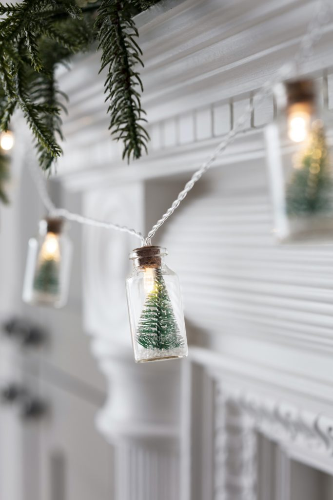 little glass bottles with christmas tree lights inside