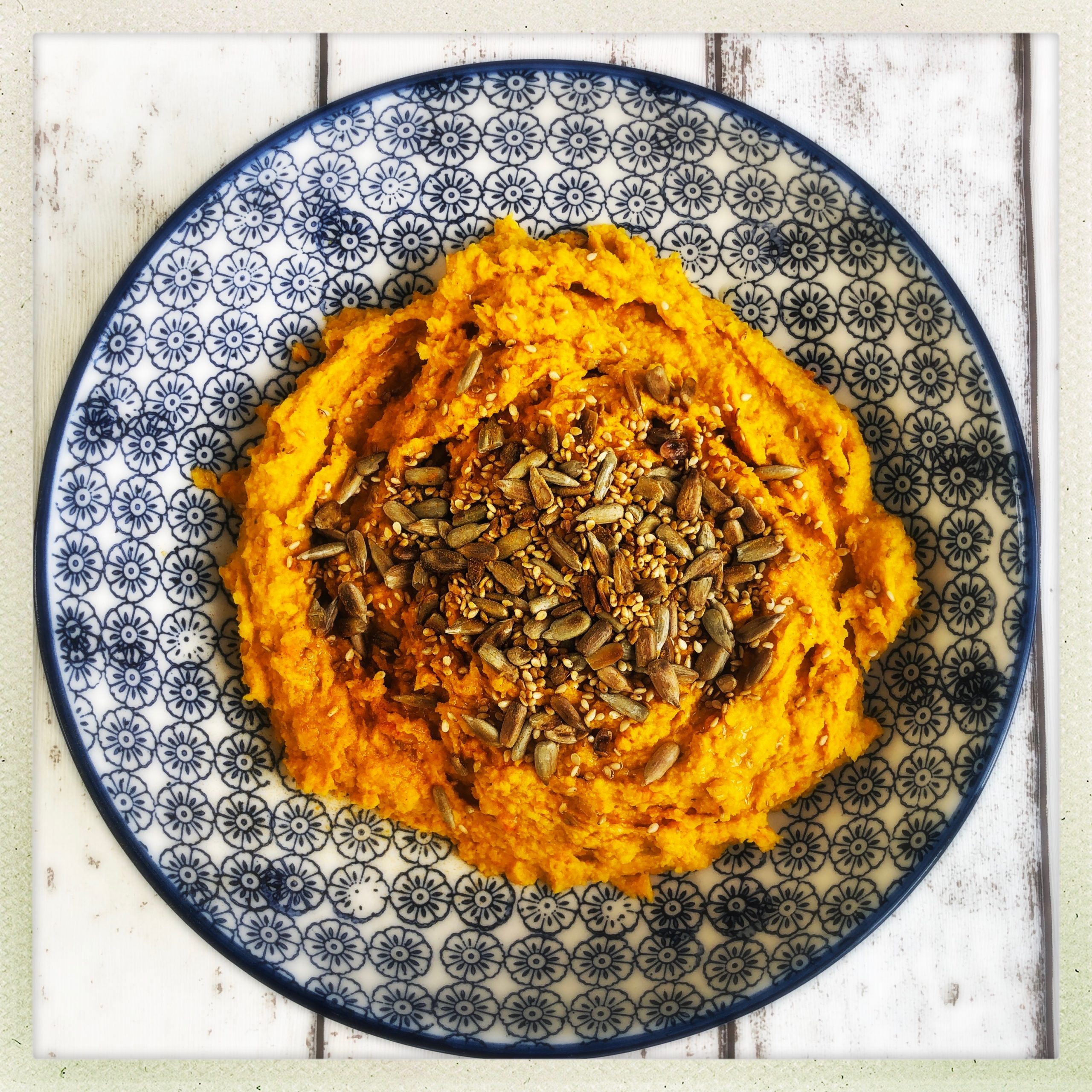 blue and white bowl filled with homemade carrot hummus topped with toasted seeds.
