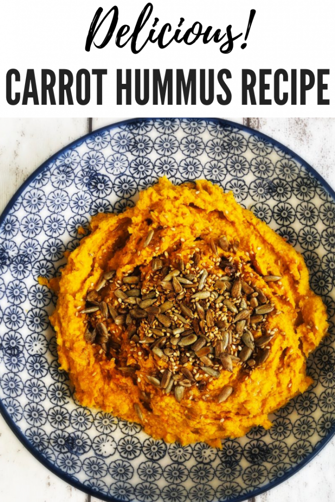 """carrot hummus scattered with sunflower seeds. Text overlay reads """"delicious carrot hummus recipe"""""""