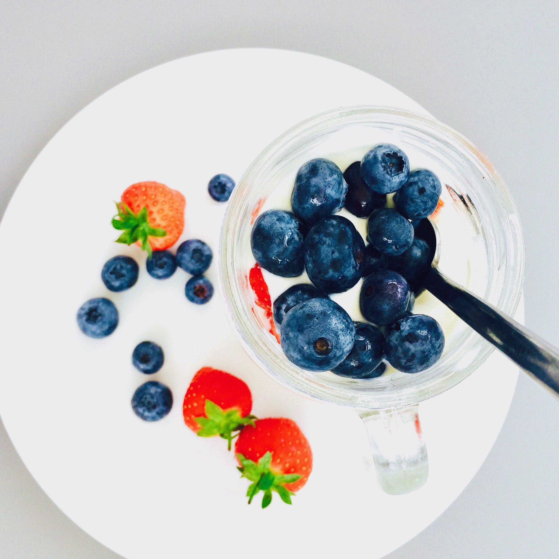 cereal sundae in a mason jar - layers of banana, greek yogurt, strawberries and blueberries