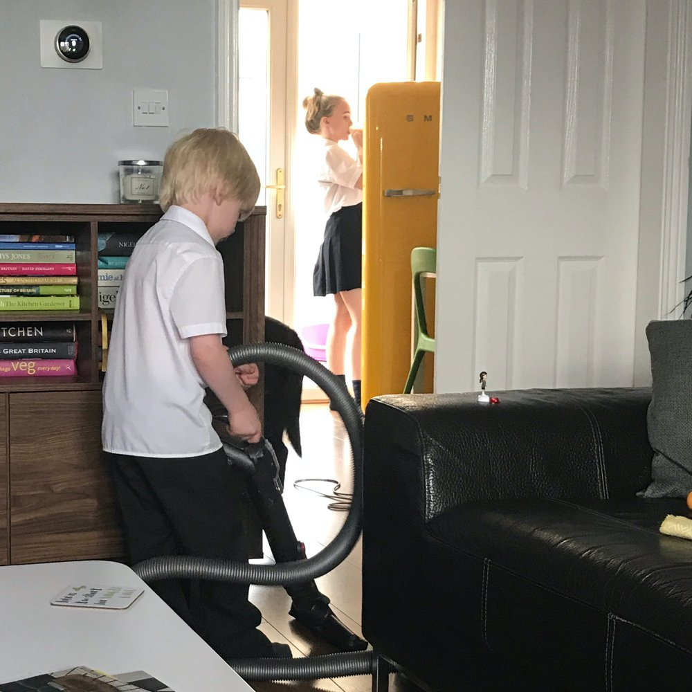 young boy vacuuming the liiving room