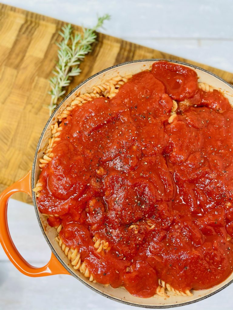 meatball pasta bake being topped with tomato sauce before the cheese is added