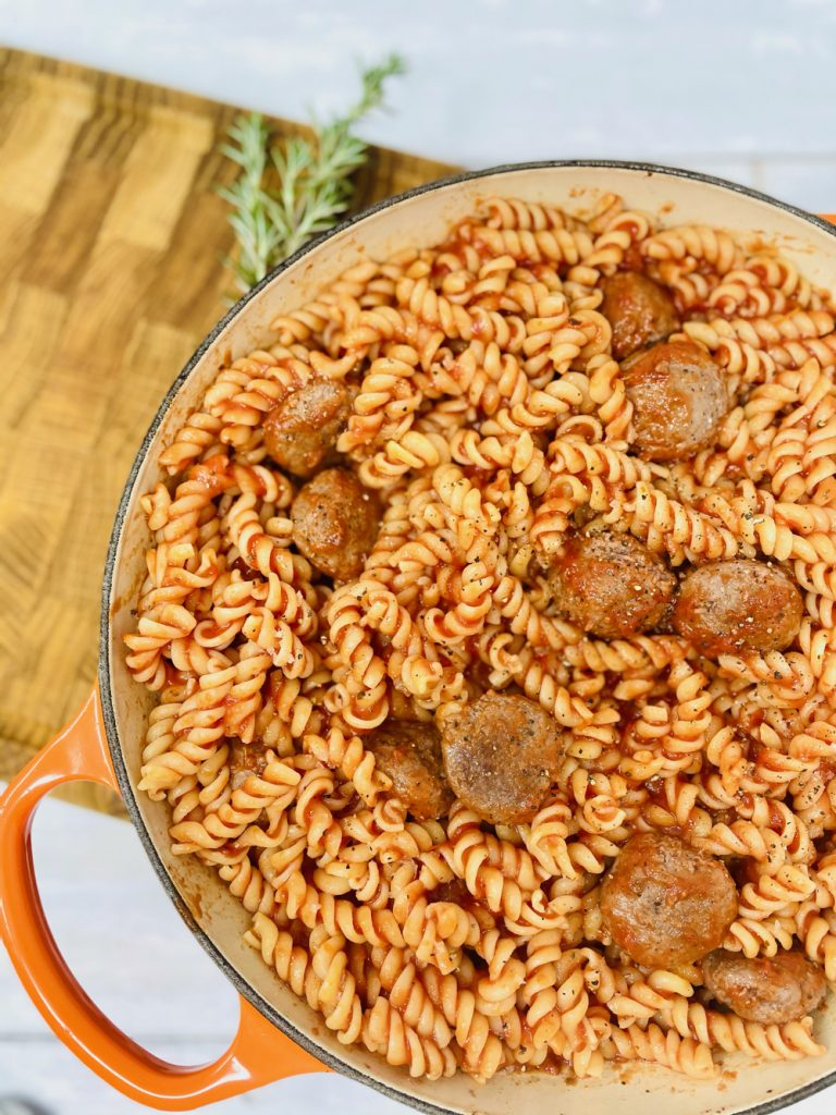 fusilli tossed in tomato sauce and mixed with meatballs ready to be turned into meatball pasta bake