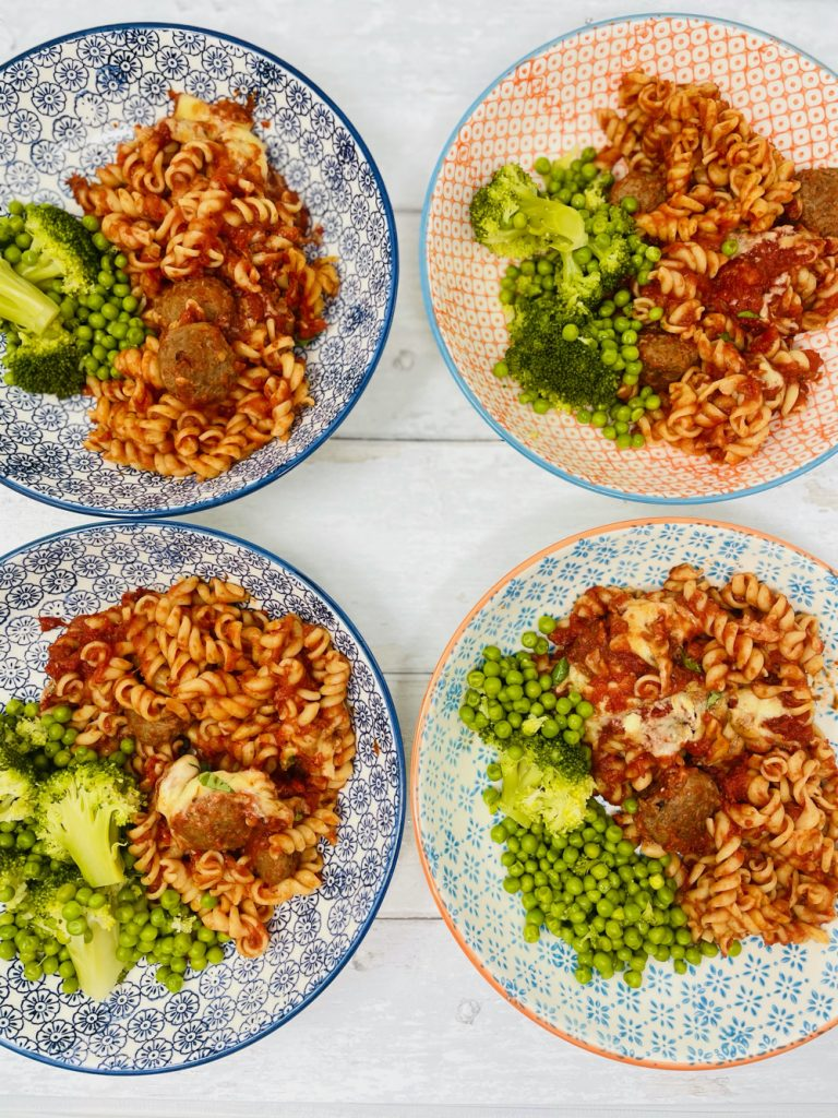 meatball pasta bake served with broccoli and peas