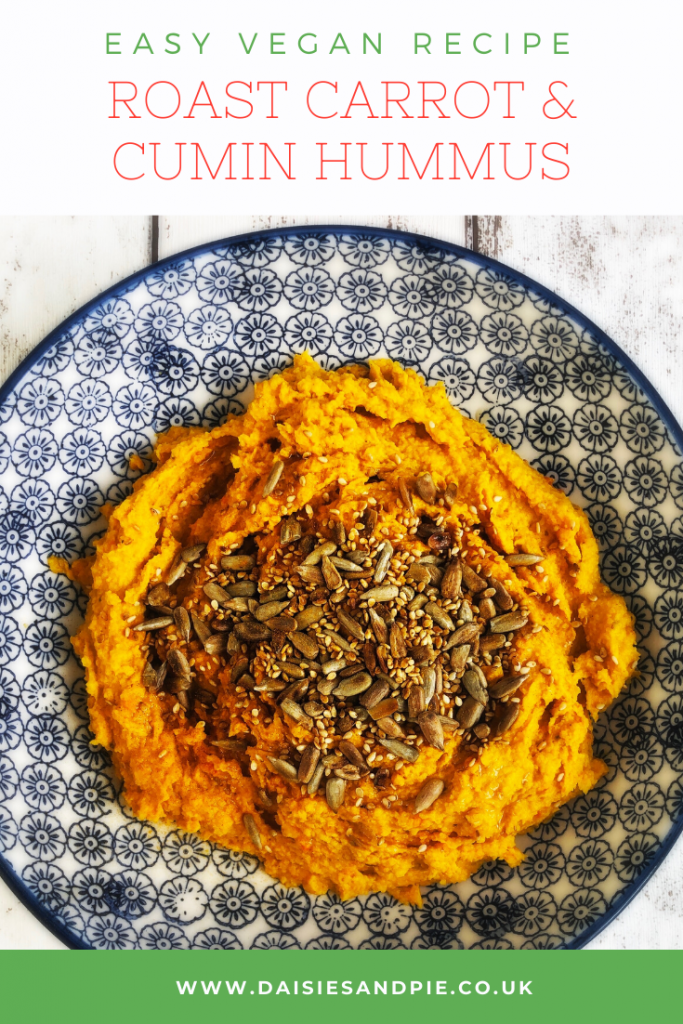 """blue and white bowl filled with homemade carrot hummus topped with toasted seeds. Text """"easy vegan recipe - roast carrot and cumin hummus - www.daisesandpie.co.uk"""""""
