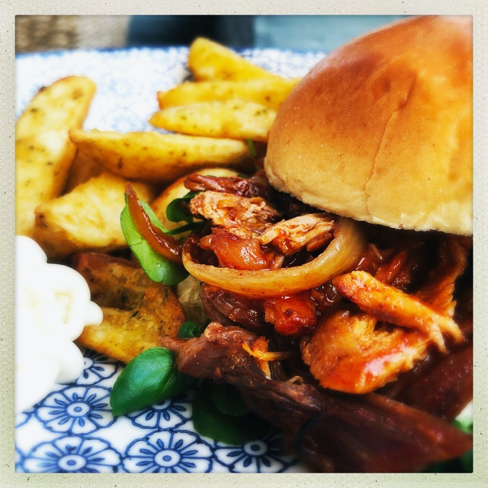 slow cooker pulled pork with peppers and onions in a BBQ marinade served with watercress salad on a toasted brioche bun. Pile of potato wedges and soured cream dip on the side.