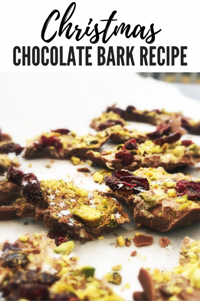 "homemade christmas chocolate bark absolutely loaded with pistachios and cranberries with a sprinkling of edible glitter and silver stars. Bark has been broken up into pieces and is on white paper background. Text overlay ""Christmas chocolate bark recipe"""