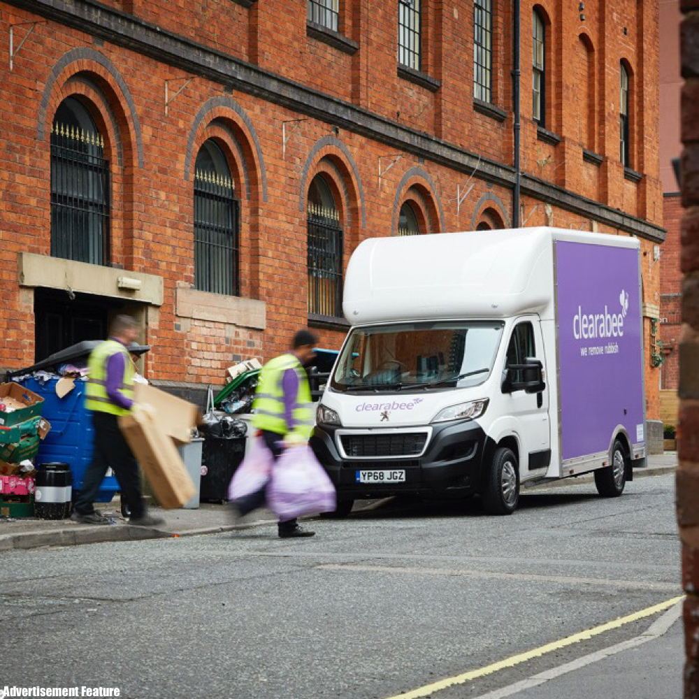Clearabee purple van parked on the road by an apartment building - two work men wearing hi-vis yellow jackets removing domestic waste from the curb side