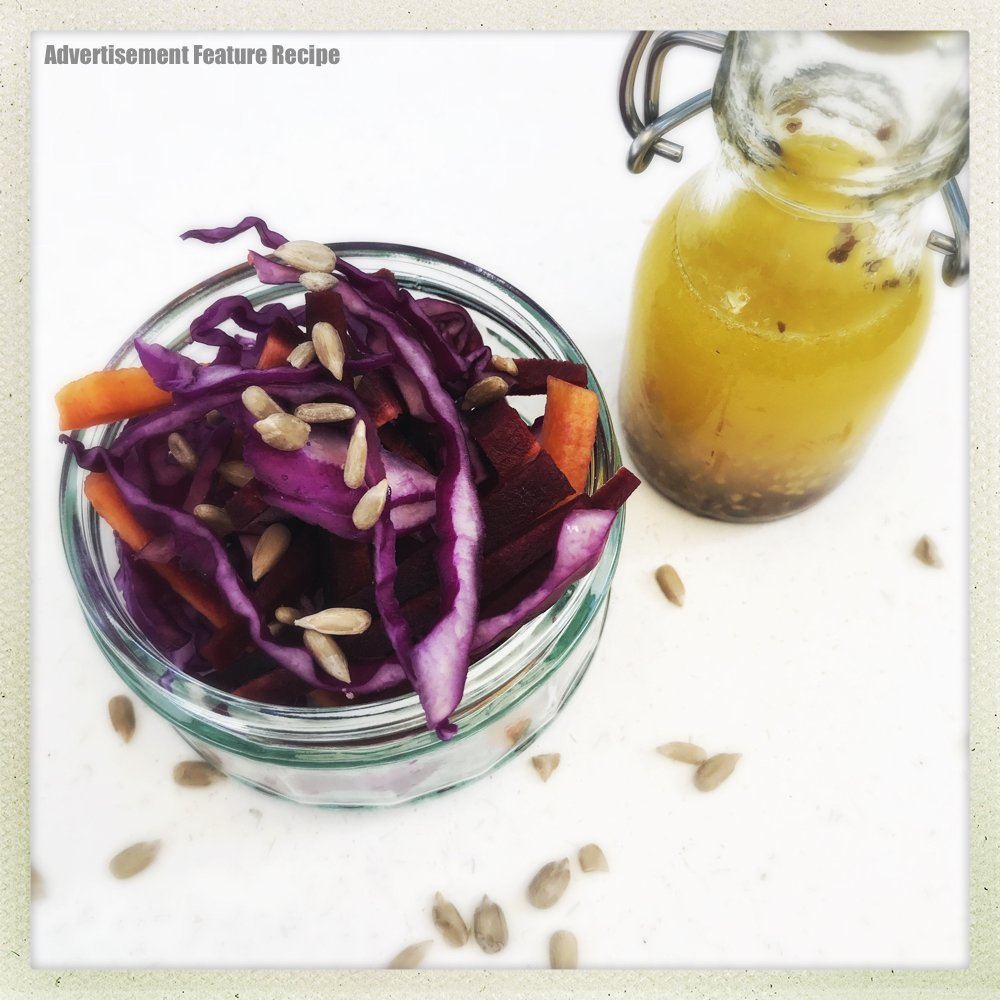 glass jar filled with homemade red coleslaw - with carrots and sunflower seeds - standing next to coleslaw is small glass bottle of salad dressing with olive oil, lemon juice and mustard
