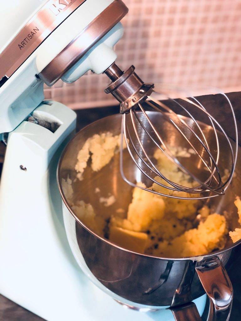 pastel blue KitchenAid fitted with the whisk blade being used to make mashed potatoes - bowl filled with mashed potatoes and butter ready to be whisked.