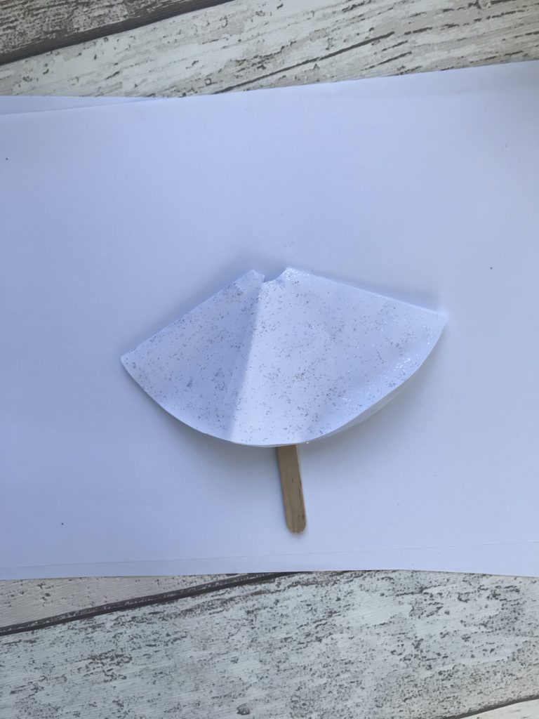 paper circle folded in half and glued onto al lollipop stick - paper semi circle decorated with glitter