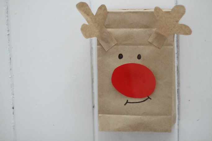 reindeer made from brown paper bag with marker pen eyes and mouth and a big red nose stuck on the front - little brown paper antlers stuck out of the top