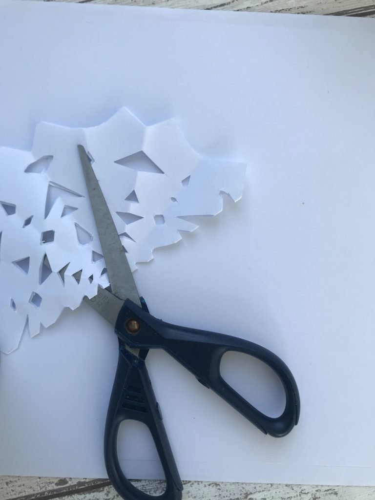 homemade paper snowflake decoration with all little shapes cut out of the paper, pair of scissors next to the snowflake.