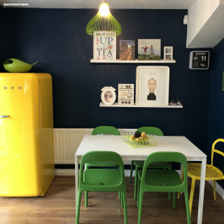 dining area - with dark midnight blue painted walls - bright yellow smeg fridge, white rectangle dining table with green plastic chairs and bright yellow metal chair. Two picture rows on the wall with images of steve jobs, kids at the beach and media city scape