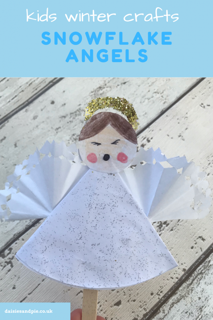 "a child made paper craft snowflake angel with glitter dress and snowflake paper wings with a glitter crown. Text ""Kids winter crafts - snowflake angel www.daisiesandpie.co.uk"""