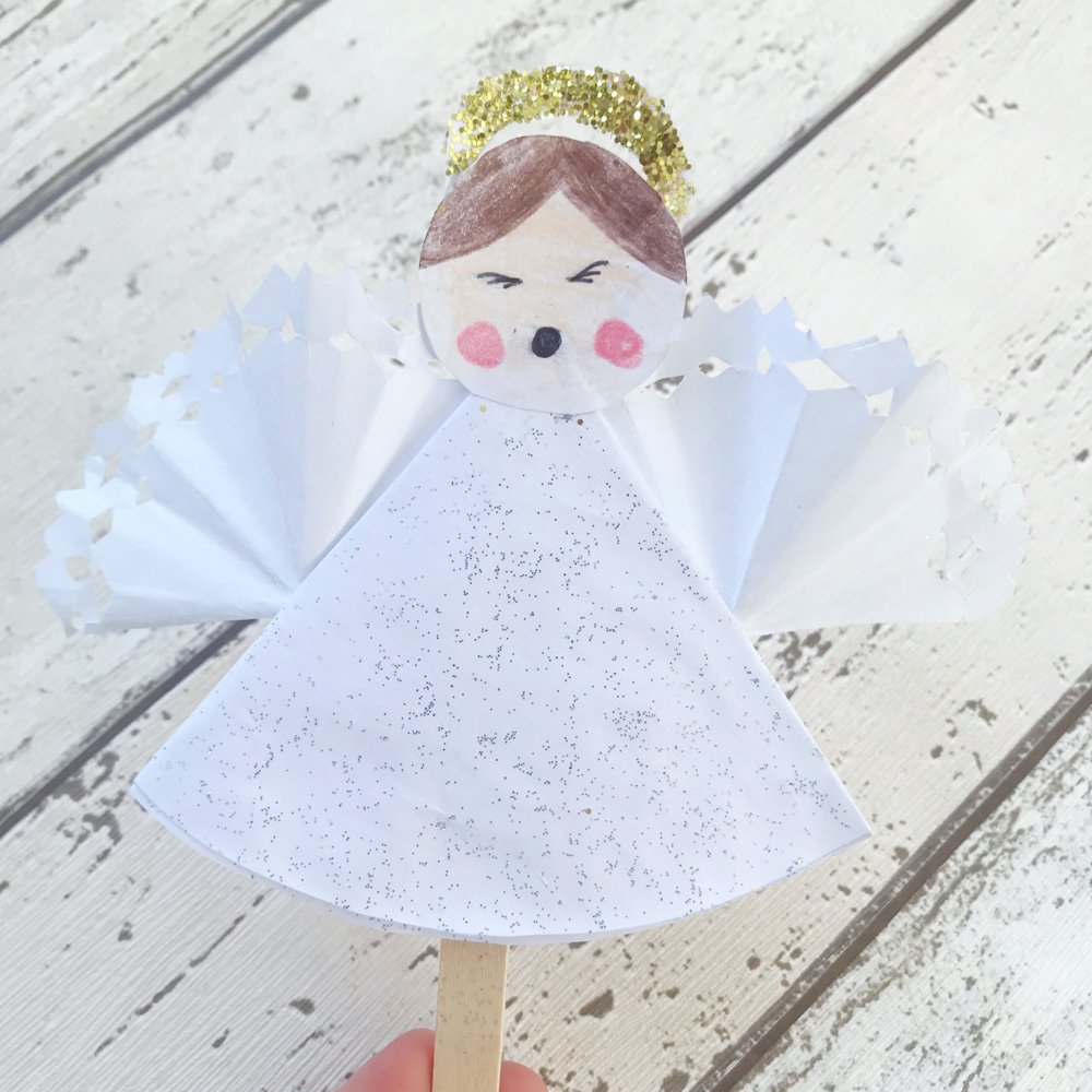 a child made paper craft snowflake angel with glitter dress and snowflake paper wings with a glitter crown