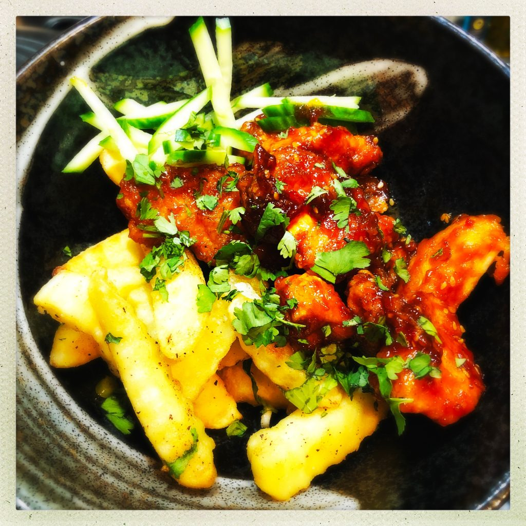 black bowl filled with Chinese style chips with spices and coriander scattered on them - served with sticky chinese chilli chicken and a little pile of cucumber ribbons