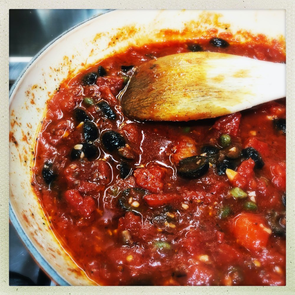 cast iron pan filled with homemade puttanesca sauce with tinned tomatoes, capers, black olives and chillies