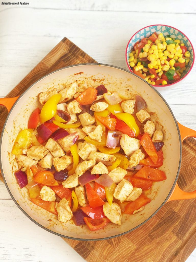 enamel pan filled with stir fried chicken, peppers and onions - flavoured with Schwartz fajita seasoning, small bowl of homemade Mexican salsa alongside the bowl - salsa is made with tinned sweetcorn, chopped tomatoes and coriander.
