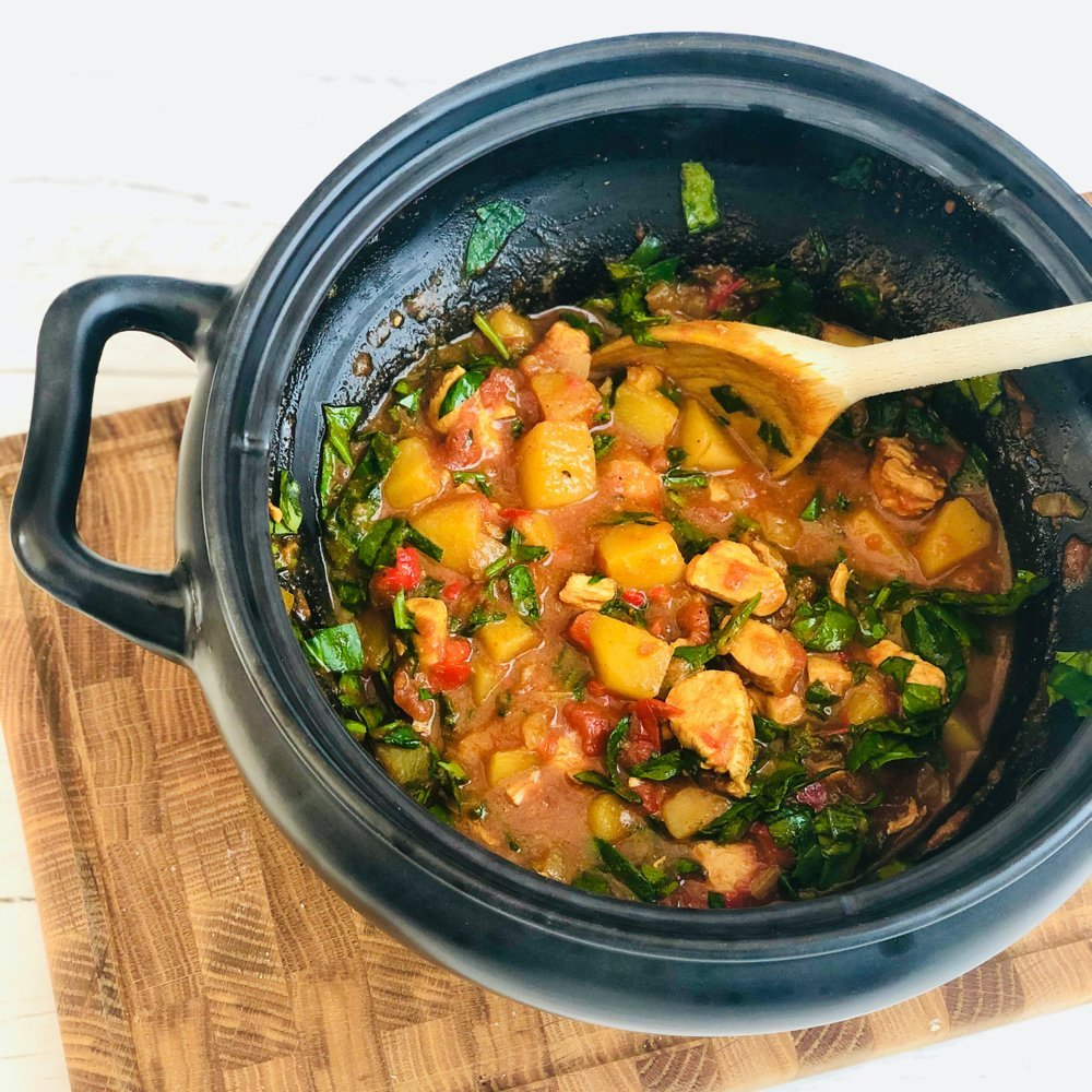 black slow cooker crockpot pan filled with cooked chicken curry with fresh chopped spinach stirred through it