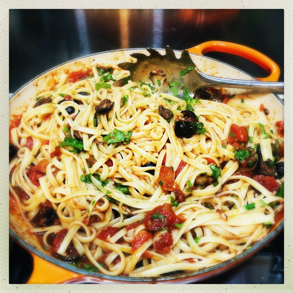 cast iron pan filled with homemade pasta puttanesca - swirls of linguine tossed in puttanesca sauce with olives, tomatoes, capers and sprinkled with flat leaf parsley