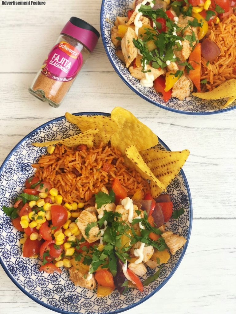 homemade chicken fajita bowls with stir fried chicken and peppers flavoured with Schwartz fajita seasoning, served in colourful bowls with homemade salsa made with sweetcorn, chopped tomatoes and coriander, served with microwave rice and nachos. Bottle of Schwartz fajita seasoning lay by the bowls
