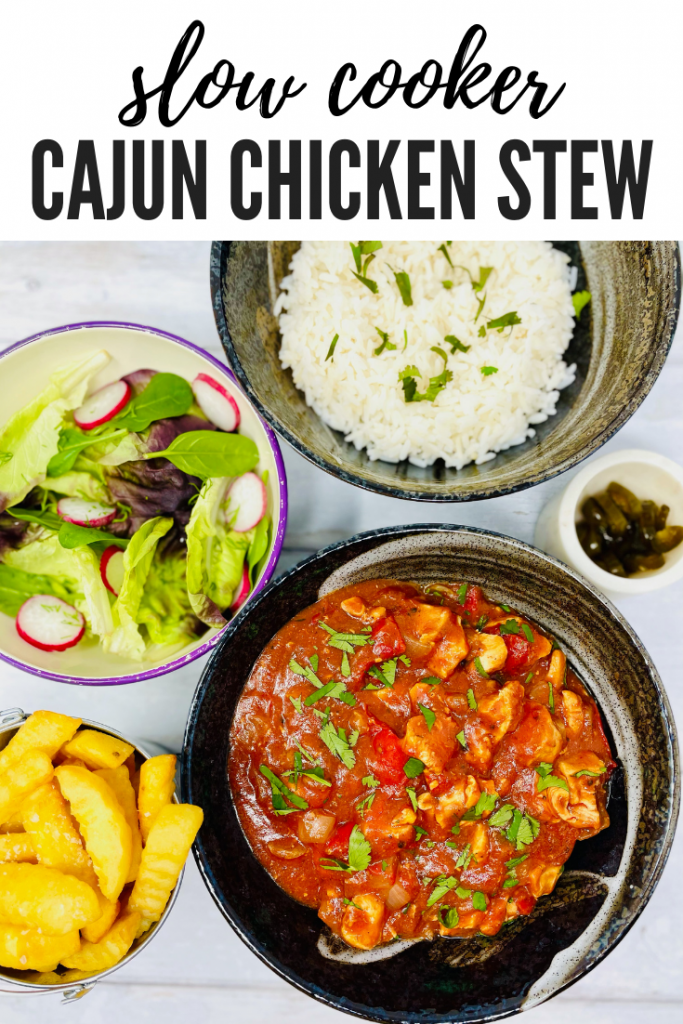 """slow cooker cajun chicken stew served with a side bowl of rice, salad and bucket of chips. Text overlay reads """"slow cooker cajun chicken stew"""""""