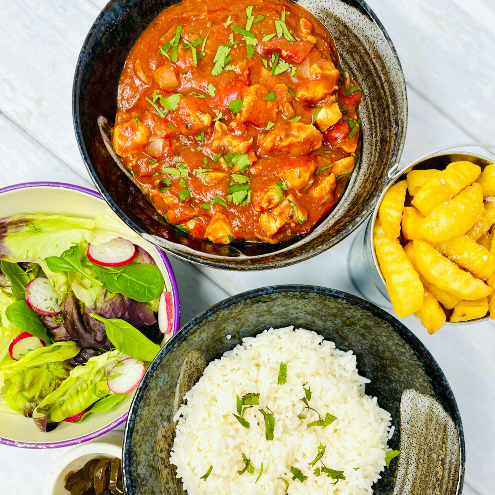 slow cooker cajun chicken stew served with a side bowl of rice, salad and bucket of chips