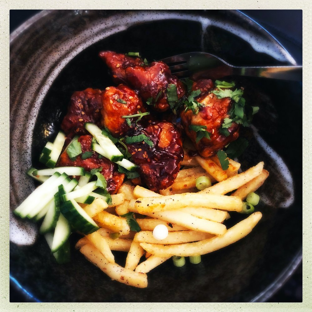 sticky chinese chicken served in a black bowl with salt and pepper chips and cucumber slices