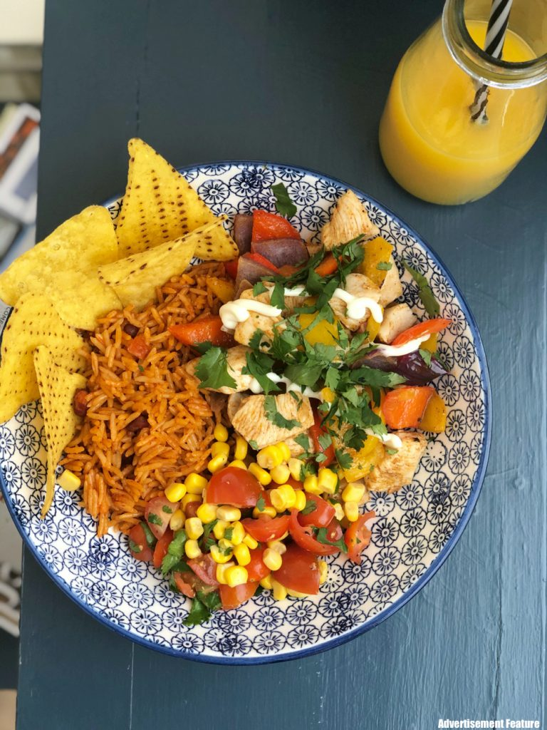 homemade chicken fajita bowls with stir fried chicken and peppers flavoured with Schwartz fajita seasoning, served in colourful bowls with homemade salsa made with sweetcorn, chopped tomatoes and coriander, served with microwave rice and nachos. Bottle of fresh orange juice with black and white striped straw by the bowl.