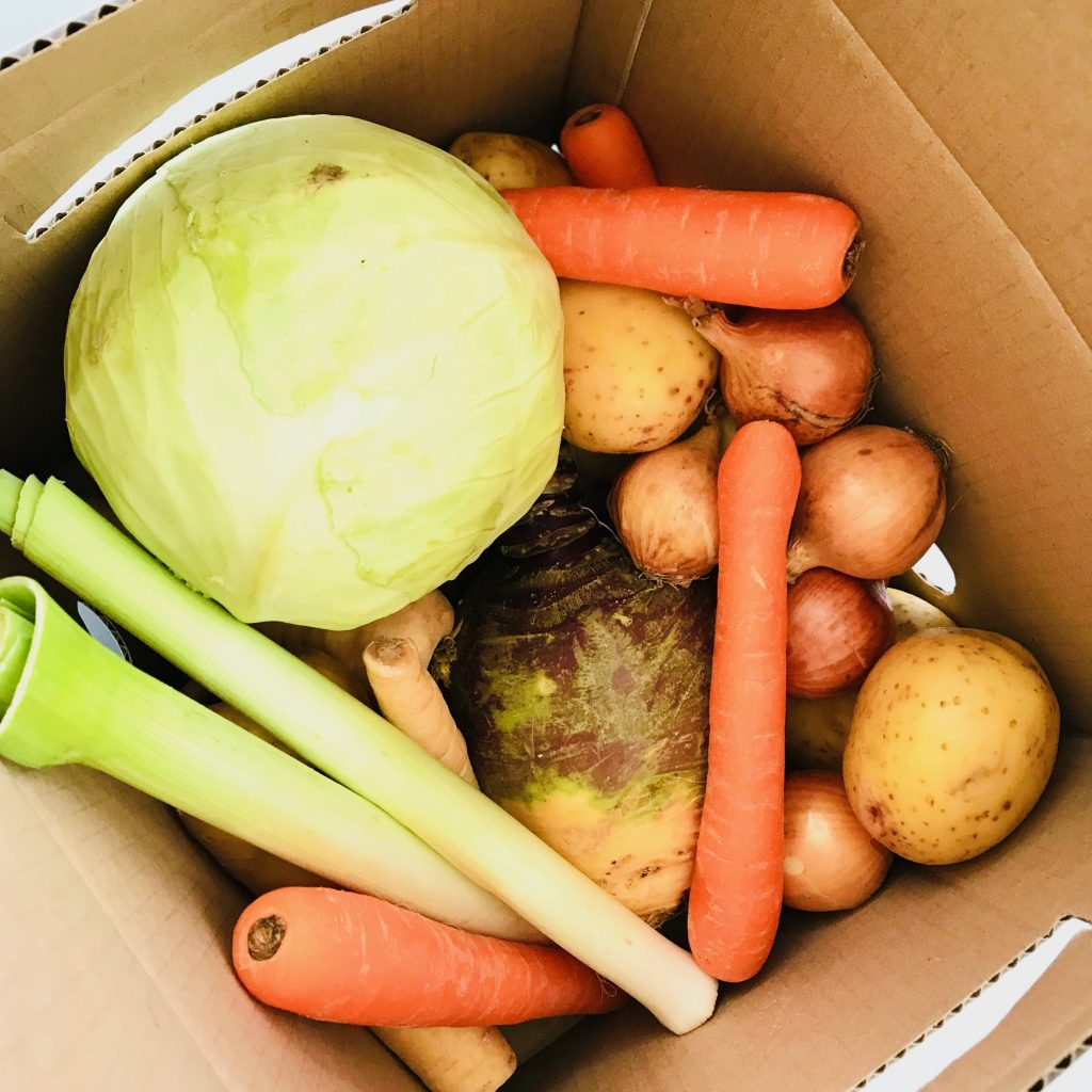 cardboard box of vegetables - carrots, swede, potatoes and leeks