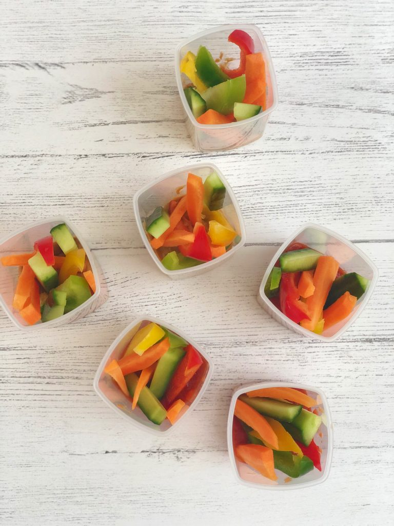 little snack pots filled with dip and vegetable sticks