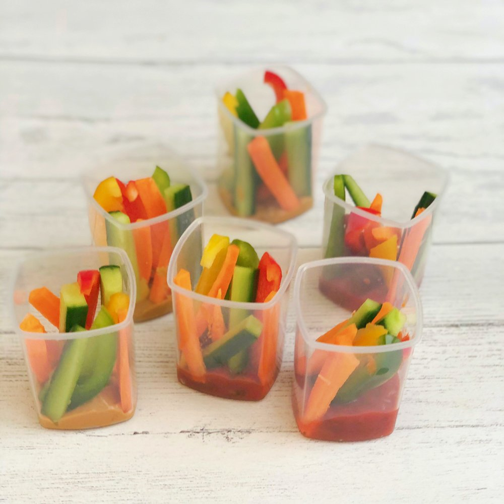 little pots with veggie sticks and peanut butter and tomato salsa in the bottom