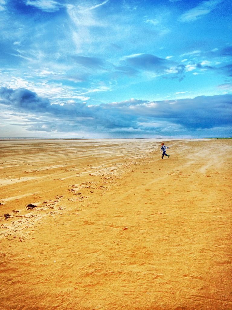 enormous empty beach at Lytham St Annes - the sea is right out on the horizon and there is only one young boy running around on an empty beach in the sunshine with bright blue skies.