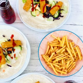 fish finger wraps with lettuce, cucumber, fish fingers, mayonnaise and drizzle of tomato ketchup, bowl of french fires and bottles of vimto also on the table