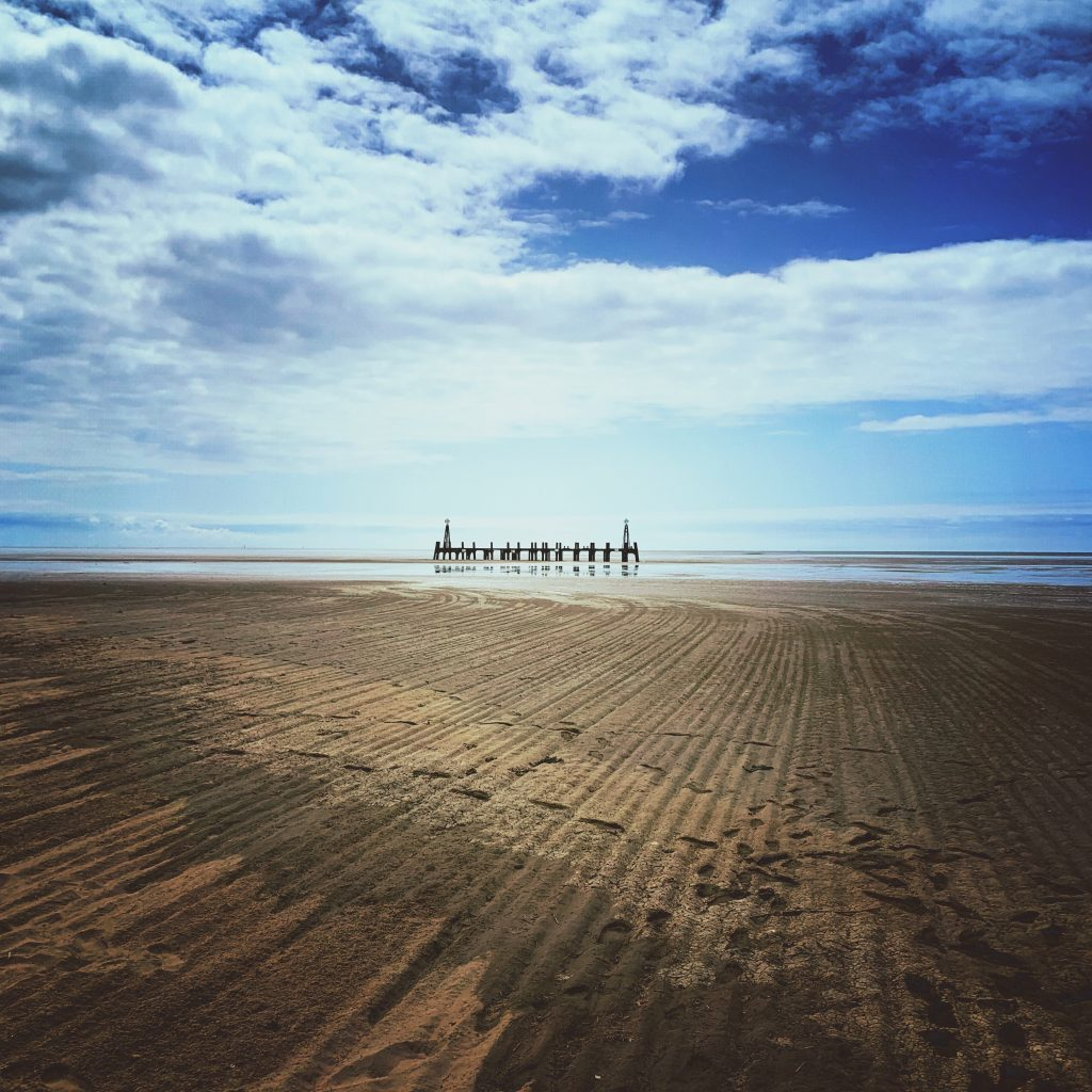 vast empty beach at Lytham St Annes with the old dilapidated pier in the background against the blue sky dotted with white clouds