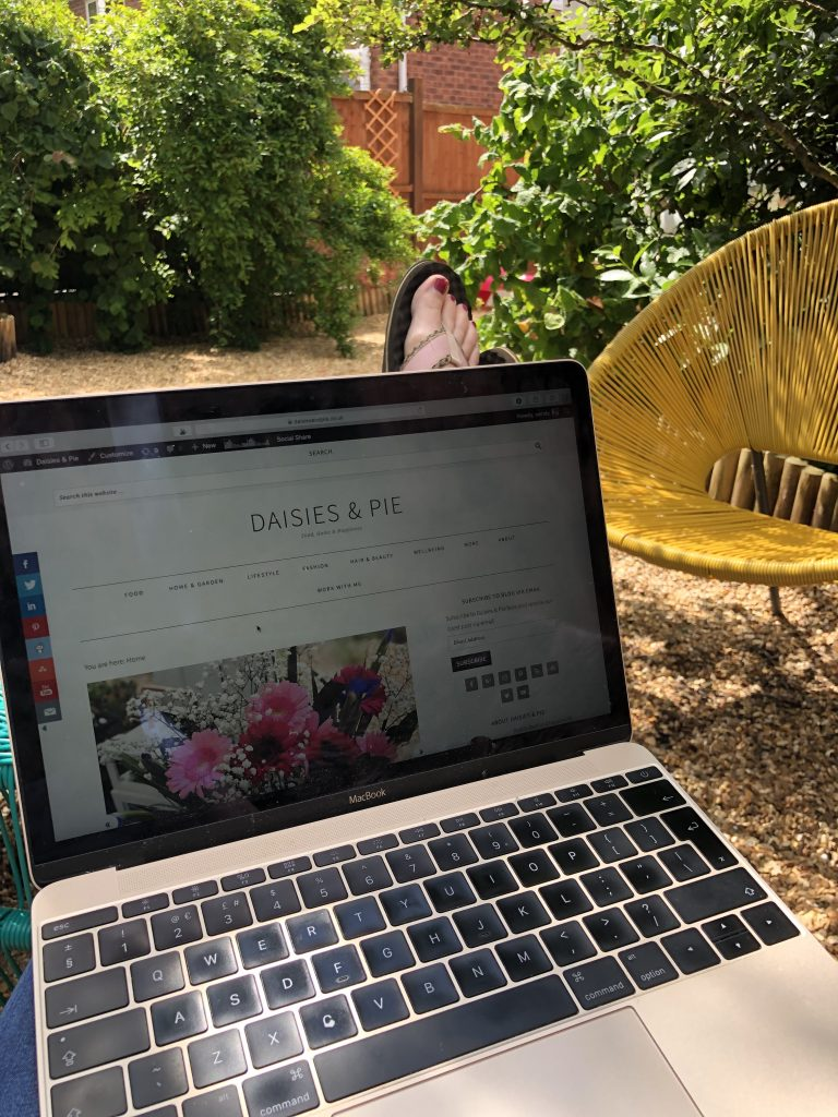 laptop in garden with Daisies & Pie website on the screen