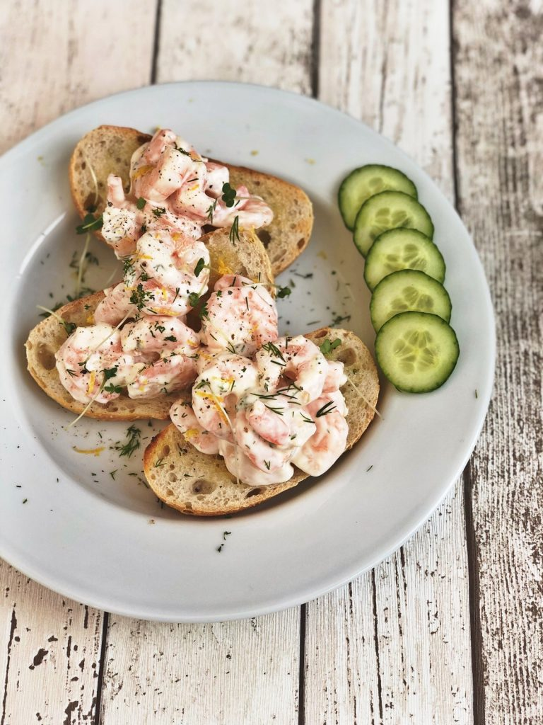 sourdough rye bread lightly toasted and topped with king prawns in a creamy dressing, sprinkled with dilll and cress, cucumber side salad next to the open sandwiches