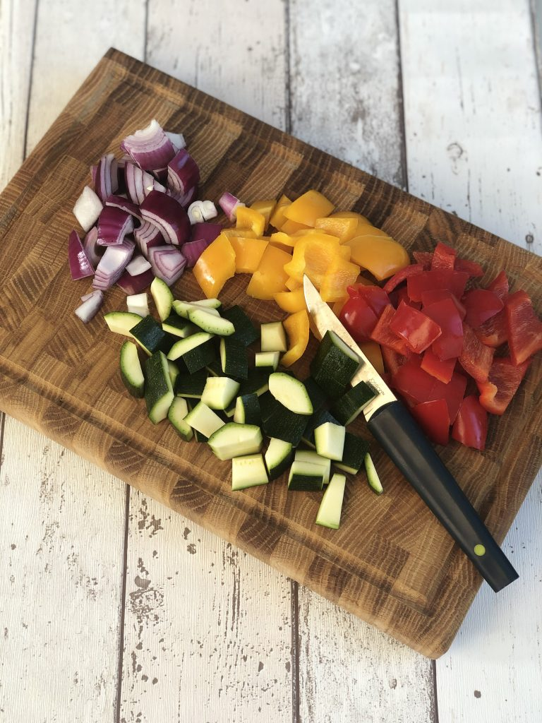 little piles of chopped courgette, red peppers, yellow peppers and red onions on a wooden chopping board with a joseph jospeh knife - chopping board is on a rustic white wooden table surface