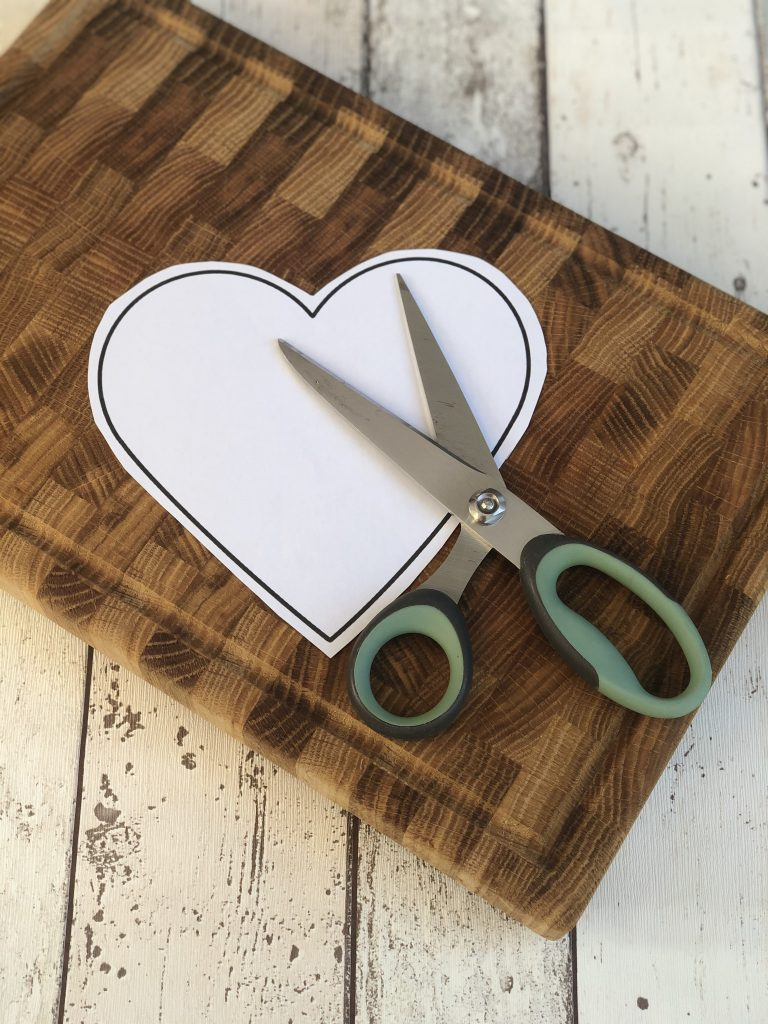 wooden chopping board with cut out white heart shape with black outline with scissors on top