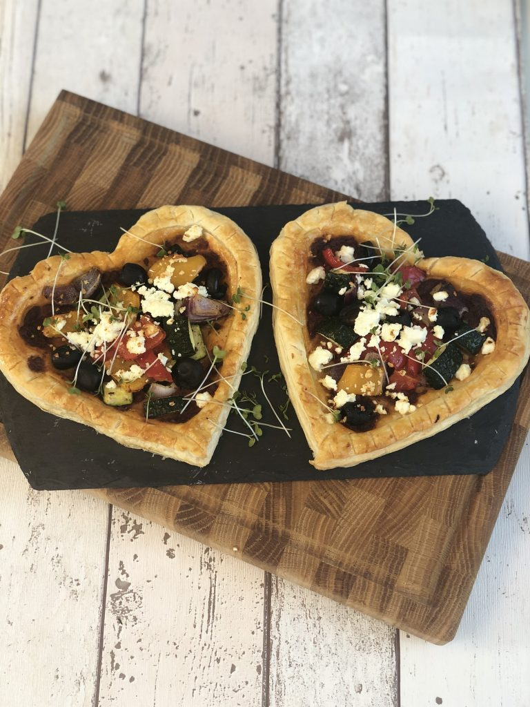 roasted vegetable tarts - two heart shaped puff pastry tarts topped with sun dried tomato pesto, roast vegetables - courgette, red and yellow peppers, red onion - black olives and feta cheese - tarts on a black slate on a rustic white table top