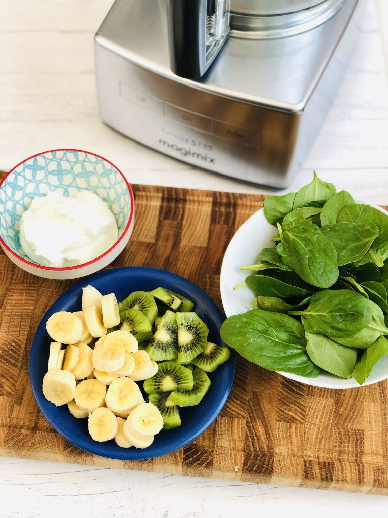 ingredients for spinach smoothie - small bowl with live natural yogurt, dark blue plate with sliced bananas and peeled chopped kiwi, white bowl with handful of baby spinach, all gathered together on a wooden block chopping board, Magimix food processor in the background