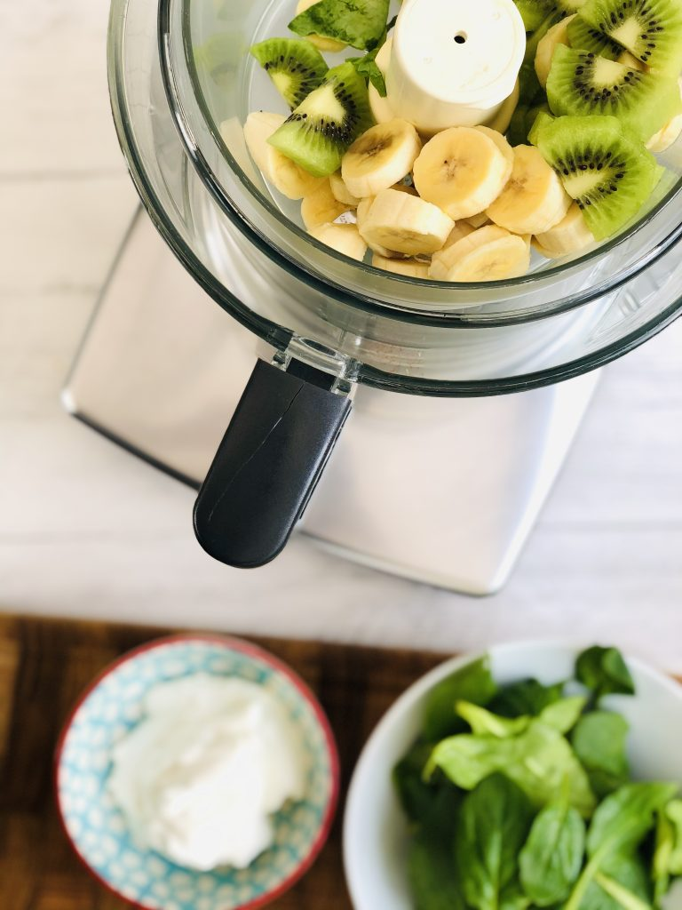 magimix food processor with the small bowl filled with sliced banana and chopped kiwi pieces, small bowl of natural yogurt and bowl of spinach on a wooden chopping board ready to be added.