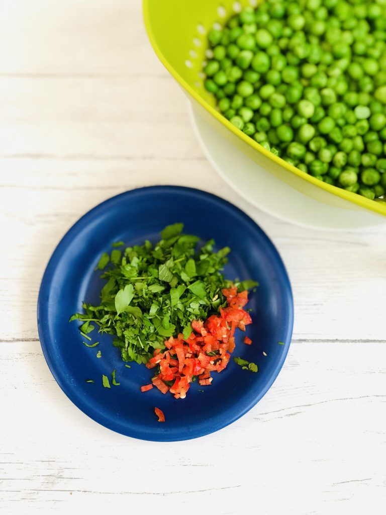 Joseph Joseph green colander filled with cooked peas, dark blue saucer with chopped flat leaf parsley and chopped chillies on a rustic white table