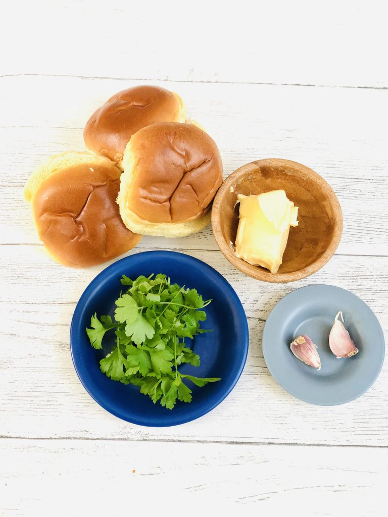 ingredients to make homemade brioche garlic bread - brioche rolls in a pile, small wooden bowl with generous knob of butter, dark blue saucer with a bunch of flat leaf parsley and small blue saucer with two unpeeled garlic cloves - all gathered together on a rustic white table top