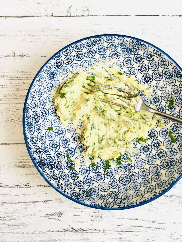 blue and white geometric flower patterned bowl with mashed butter with grated garlic and chopped flat leaf parsley stirred into it
